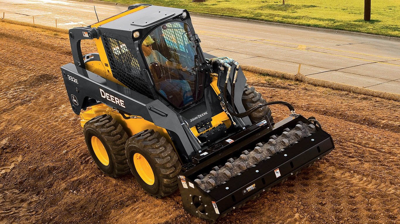 Skid Steer with vibratory roller attachment packing down dirt in a park