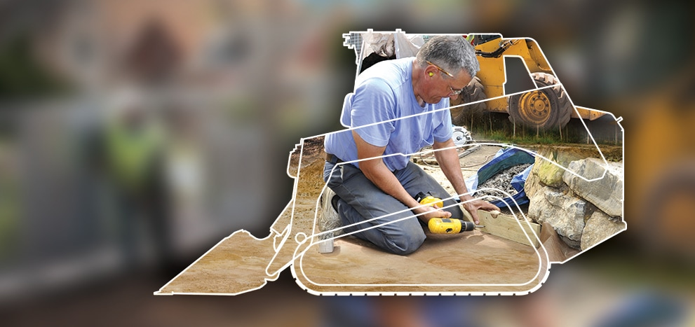 image of volunteer shown within the frame of a skid steer