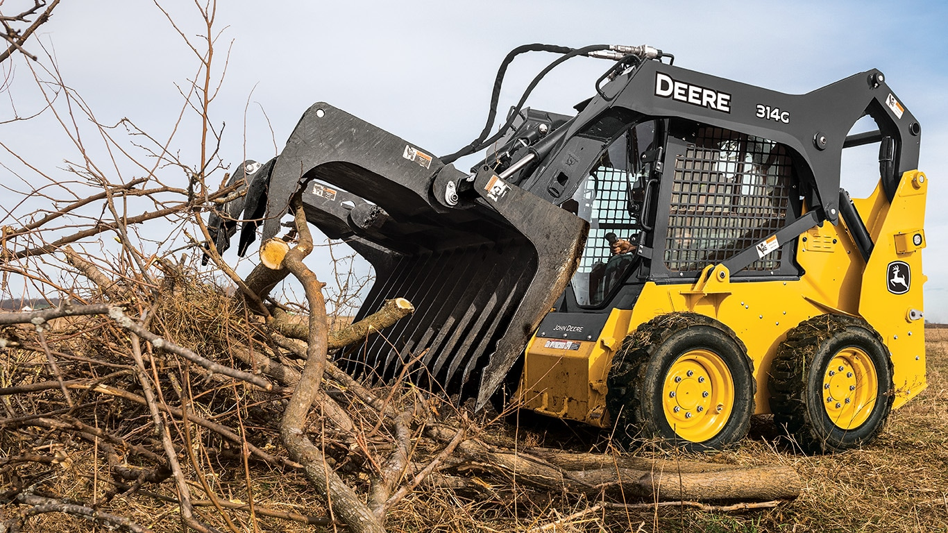 314G Skid Steer with grapple attachment picking up a load of branches and sticks.