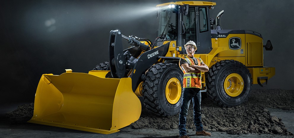 Construction worker standing in front of a 644L Mid-Size Wheel Loader on a dark background