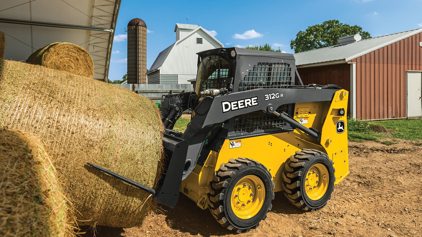 Skid steer on a farm moving a hay bale