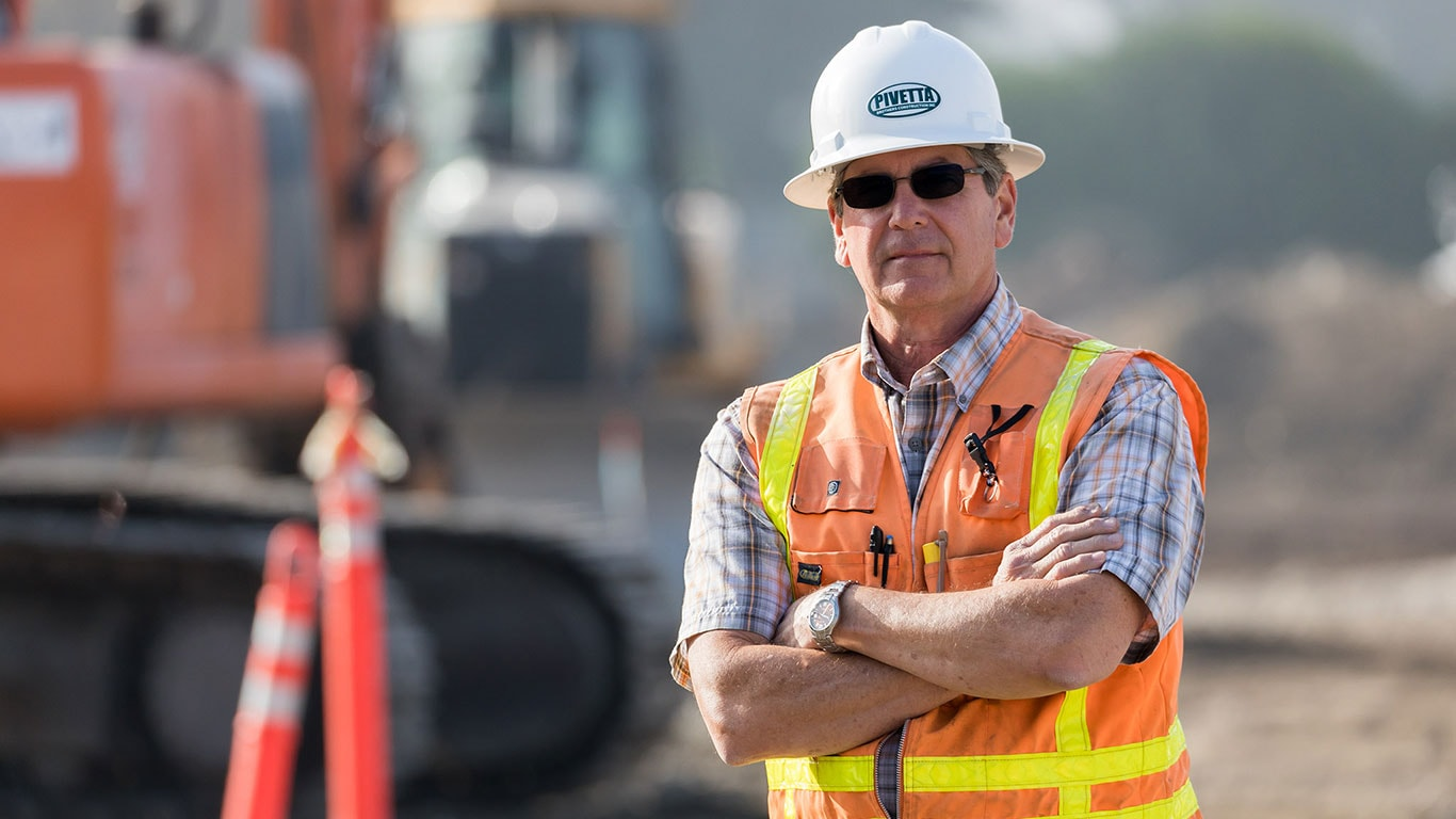 Mark Pivetta, founder and president of Pivetta Brothers Construction, stands in front of a piece of equipment.