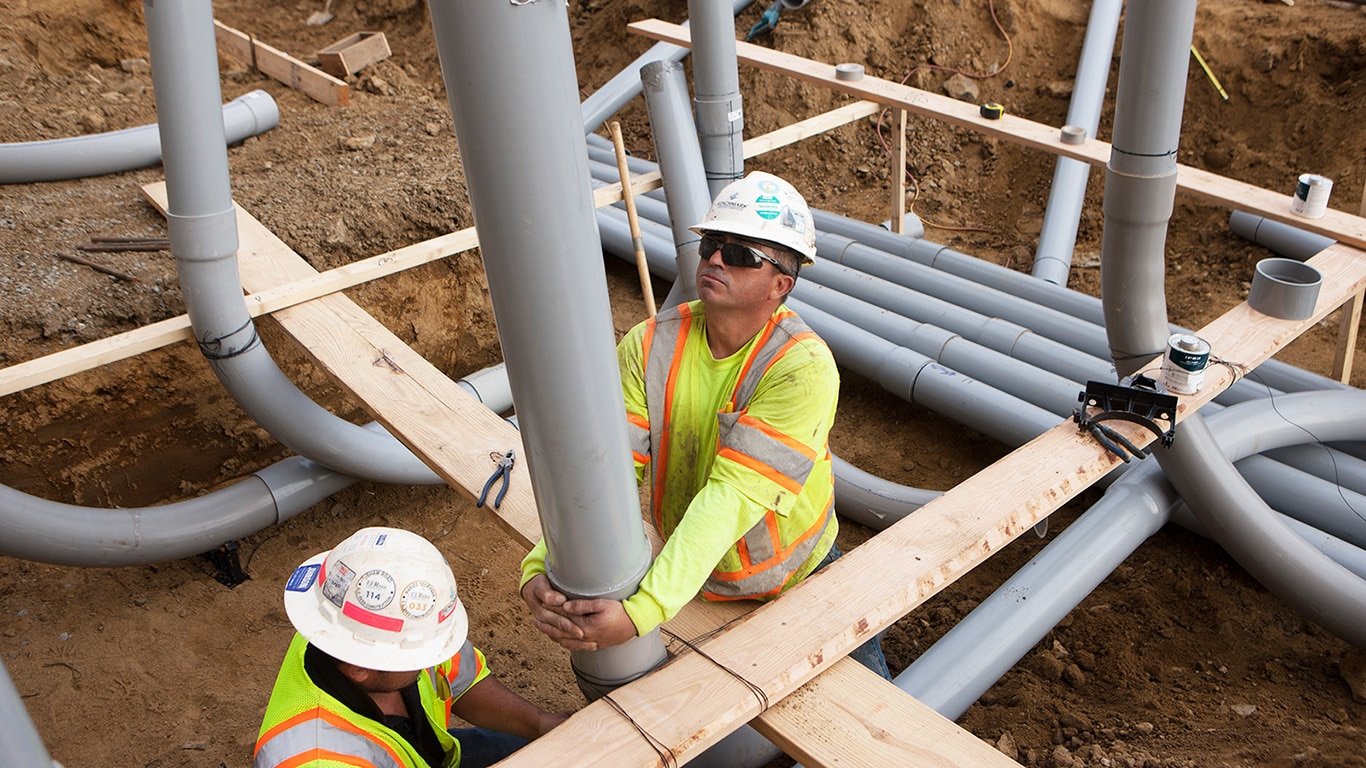 Two workers position conduit in a trench