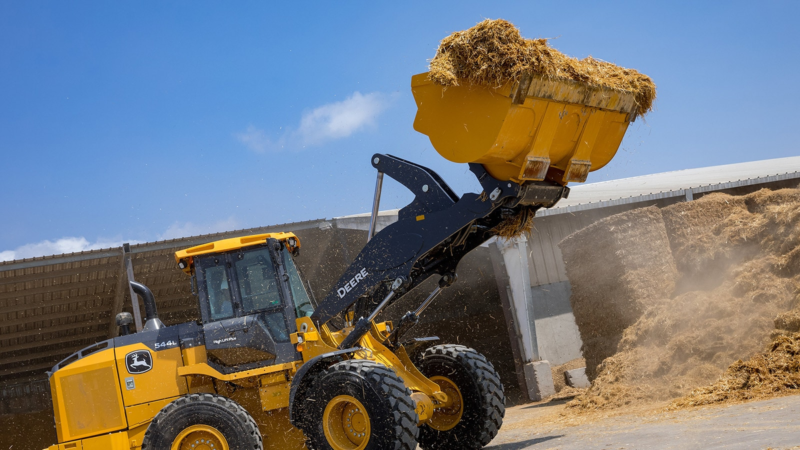544L Wheel Loader transfers loose straw from a large pile