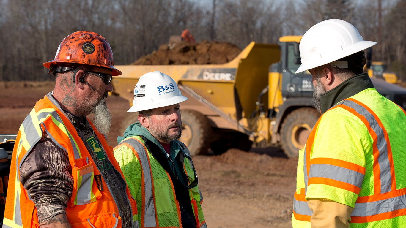 Three people talking on a site preparation jobsite with an articulated dump truck in the background