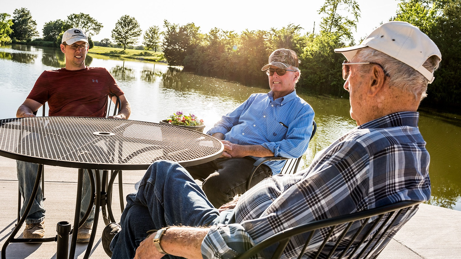 Three family members sit around a table by their pond.