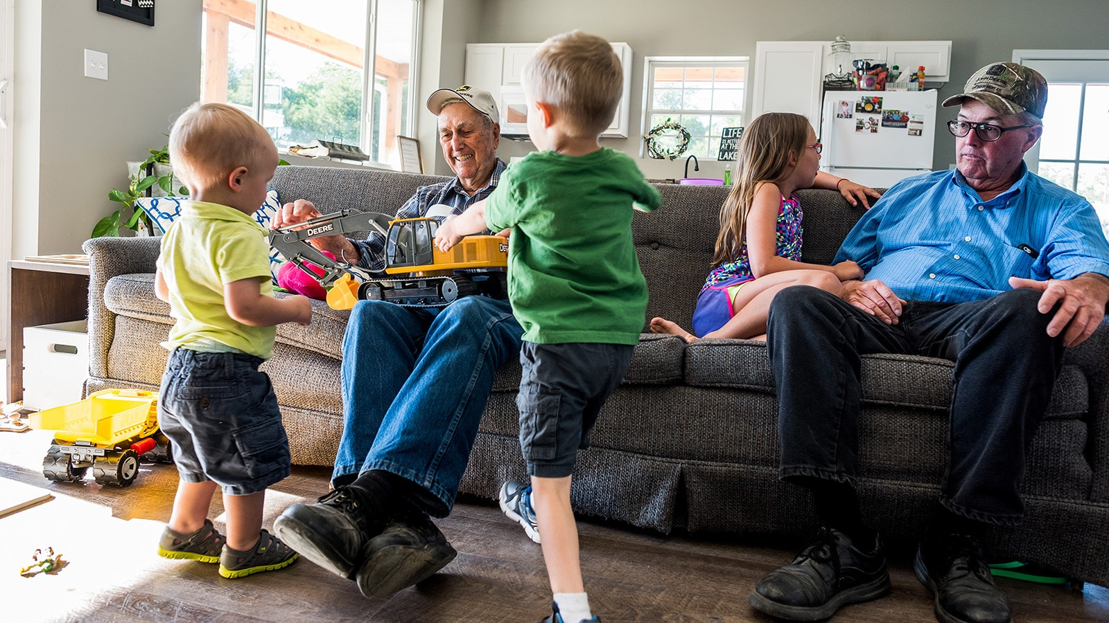 Great grandfather sitting on the couch shows a Deere excavator toy to his great-grandsons.
