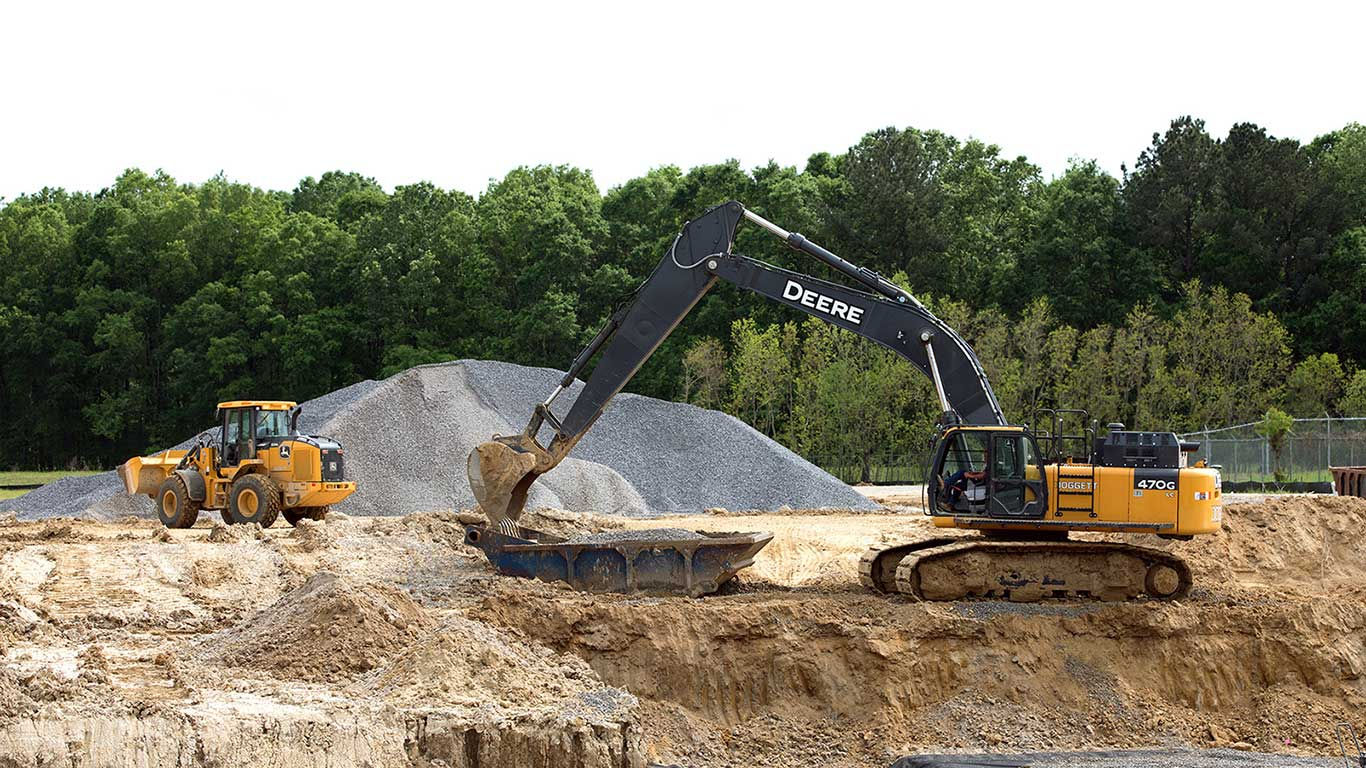 A John Deere wheel loader and 470G Excavator moving earth at a wastewater jobsite