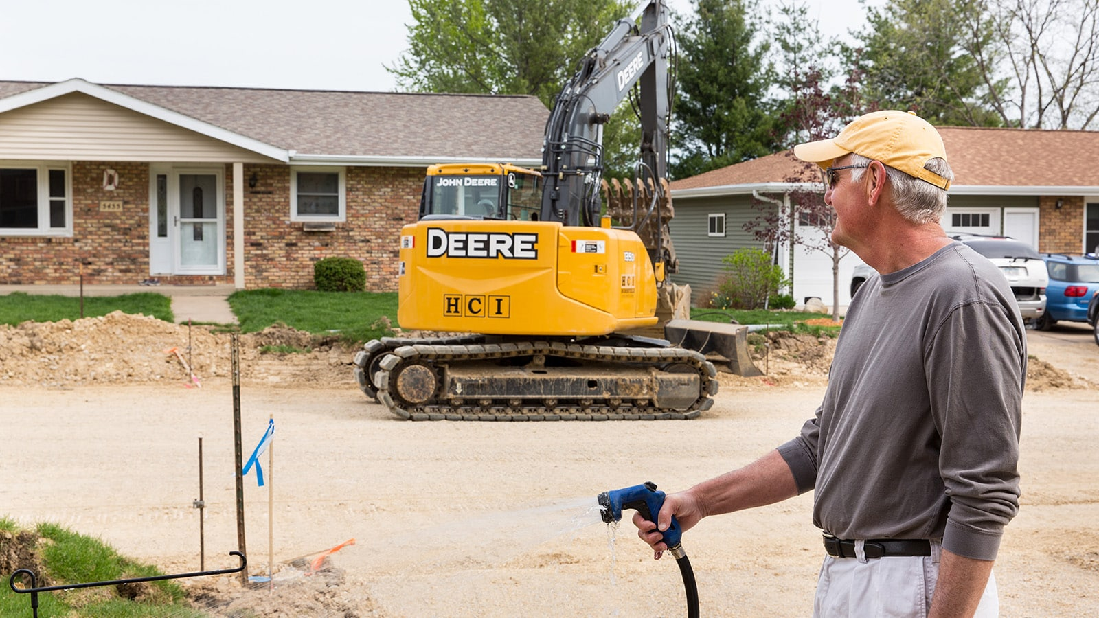 135D Excavator works in a residential neighborhood in Dubuque while a neighbor watering the lawn watches.