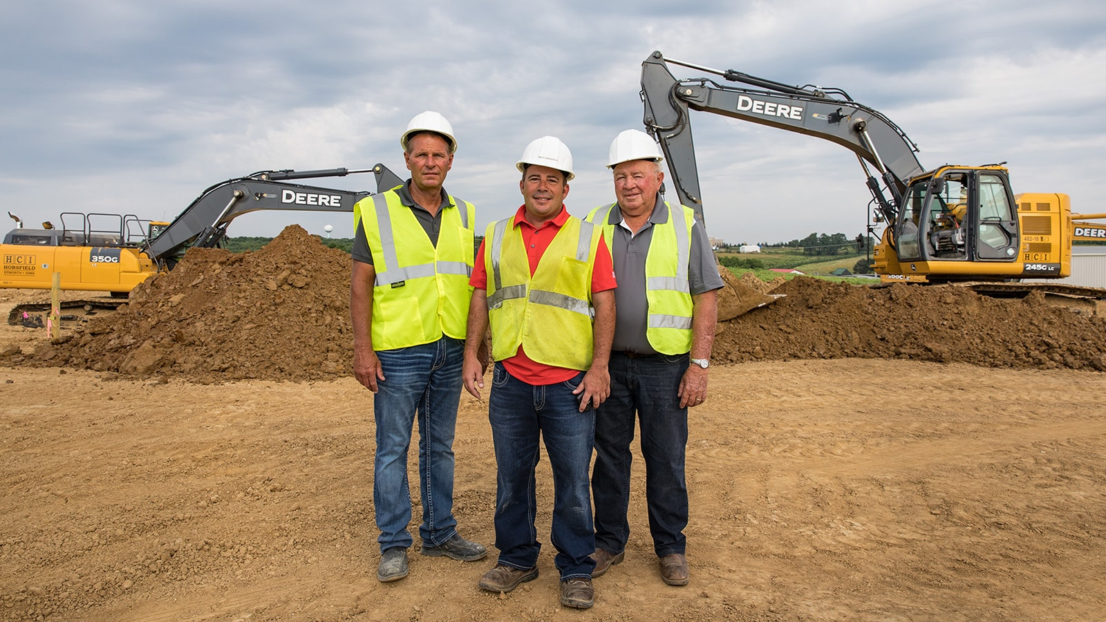 Pat, Matt and Rod Horsfield of Horsfield Companies stand in front of two of their John Deere excavators