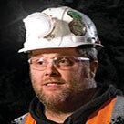 A head shot of Justin Voss wearing a hard hat and safety vest