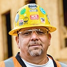 A head shot of Tim Orozco wearing a hard hat and eye protection.