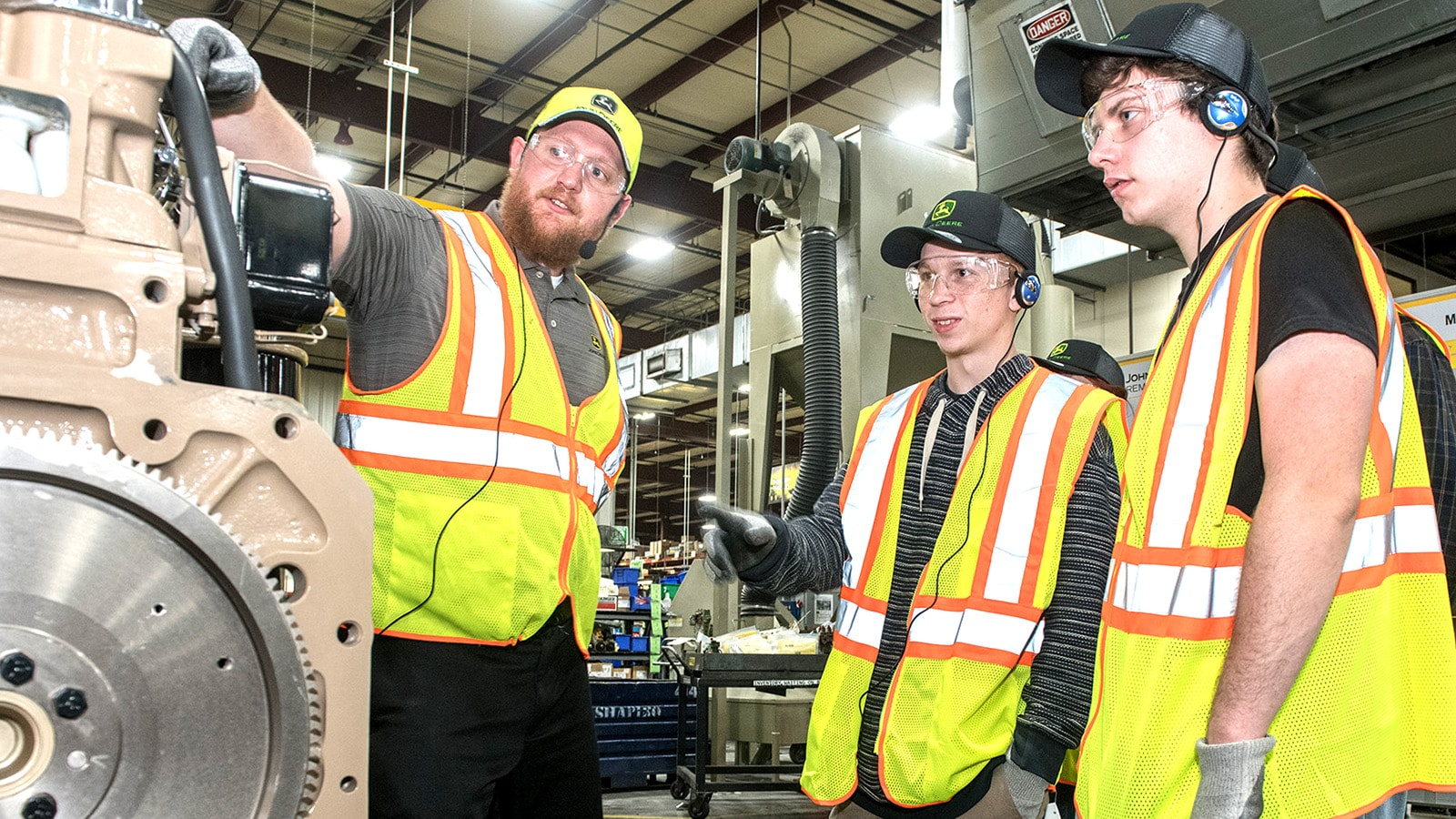 Students listen to their tour guide pointing at a remanufactured component in the Springfield facility
