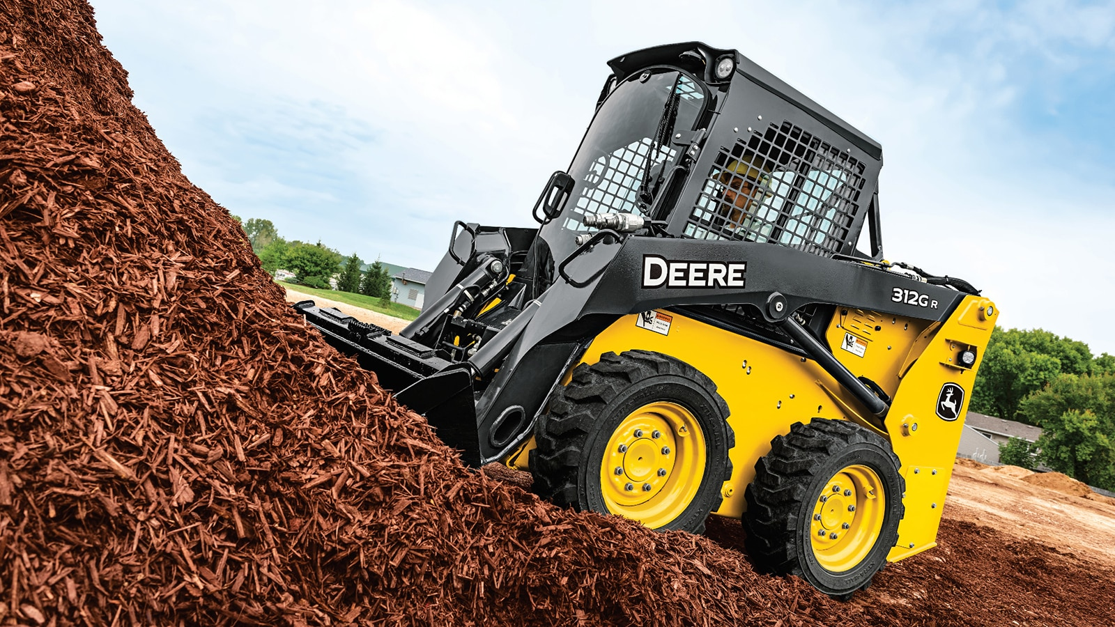 312GR Skid Steer scoops up a bucket of red mulch from a large pile