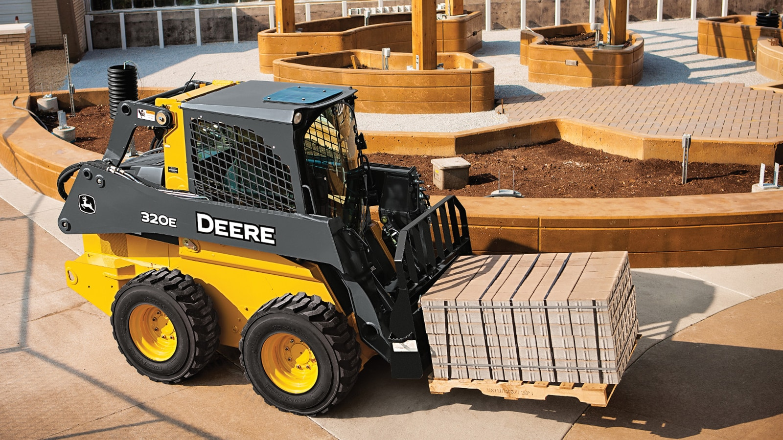 320E Skid Steer with pallet fork attachment carries a load of paving stones
