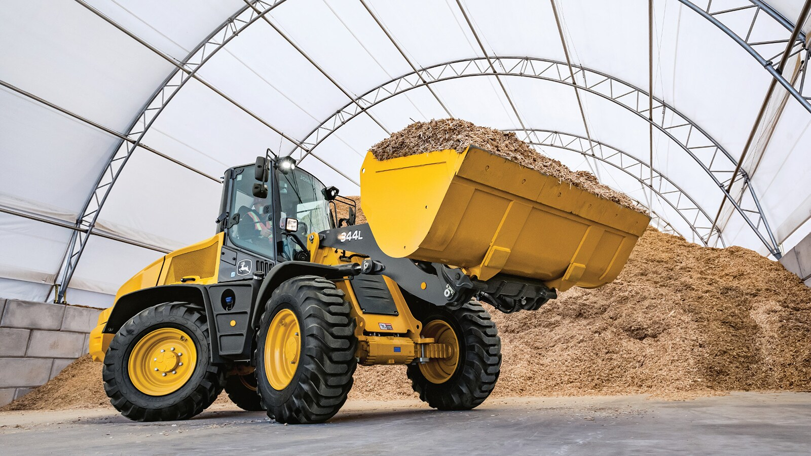 344L loader carries a bucket full of mulch inside a hoop building