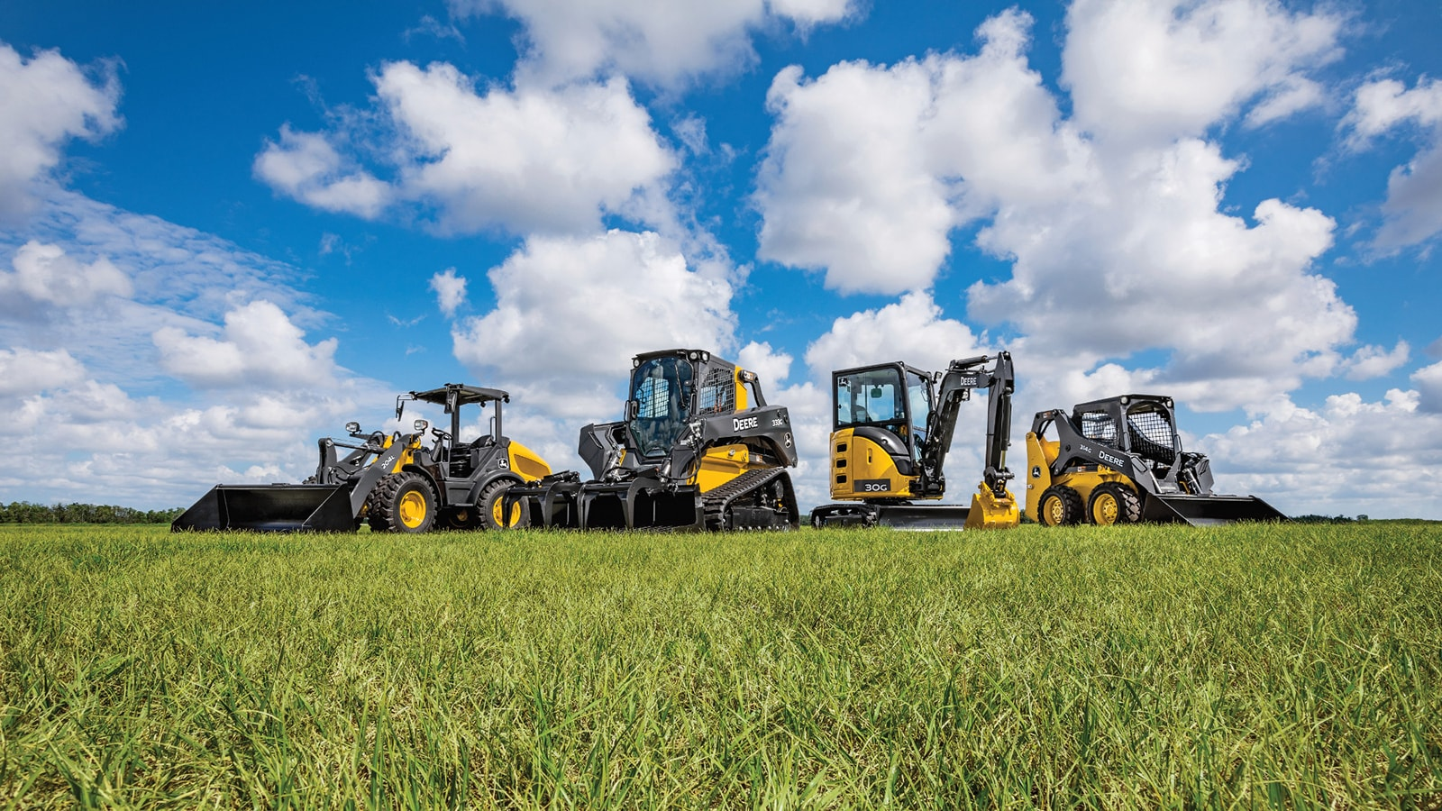 204L compact loader, 333G tracked skid steer, 30g mini excavator and 314G wheeled skid steer parked in a green grassy field with blue sky with white clouds in the background