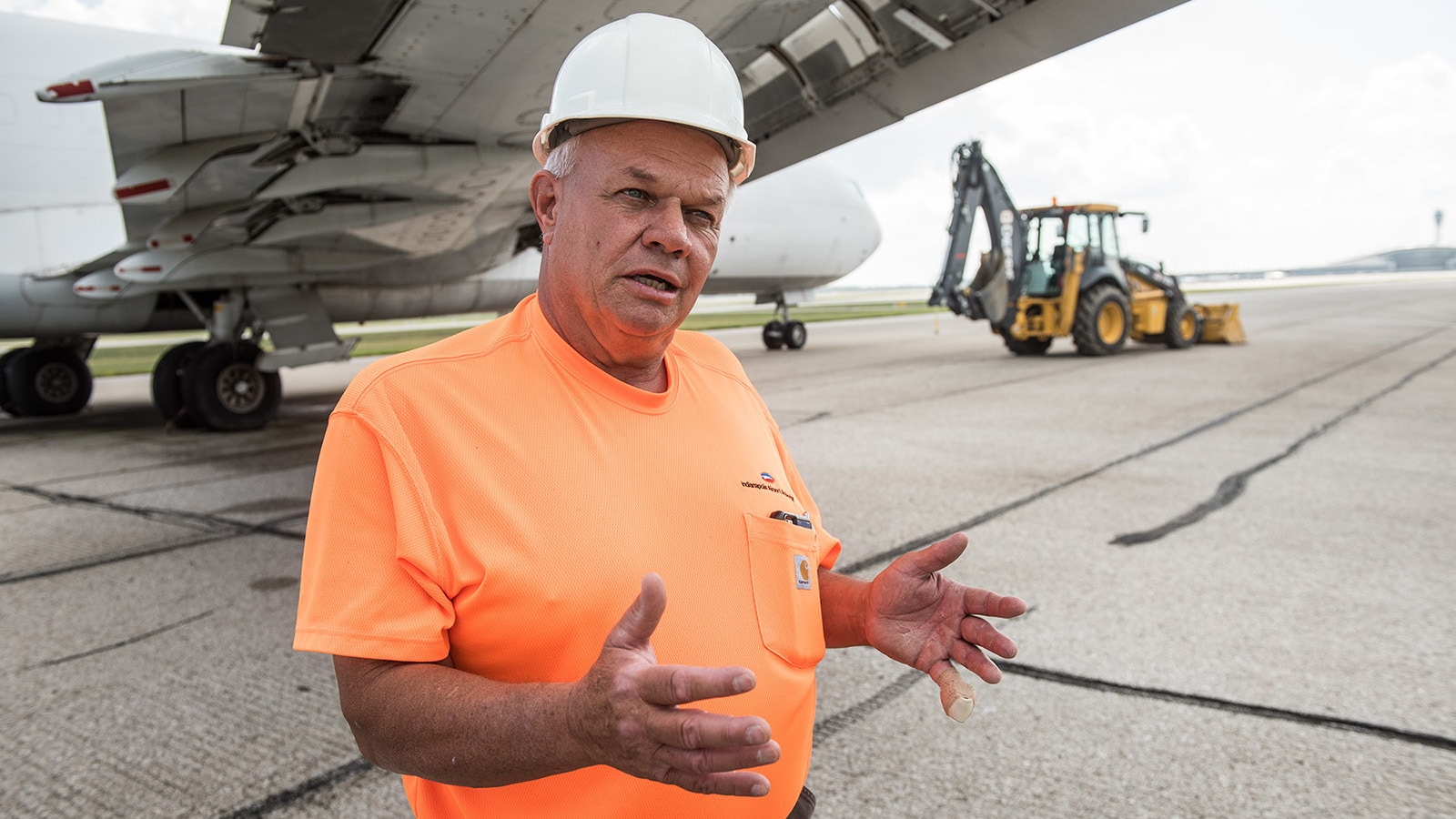 George Kestler stands under the wing of a plane with the 710L Backhoe in the background