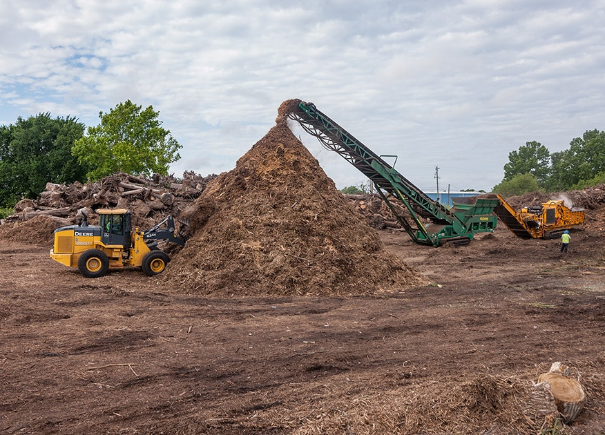 a conveyor drops mulch into a pile, while a wheel loader scoops loads off of the pile