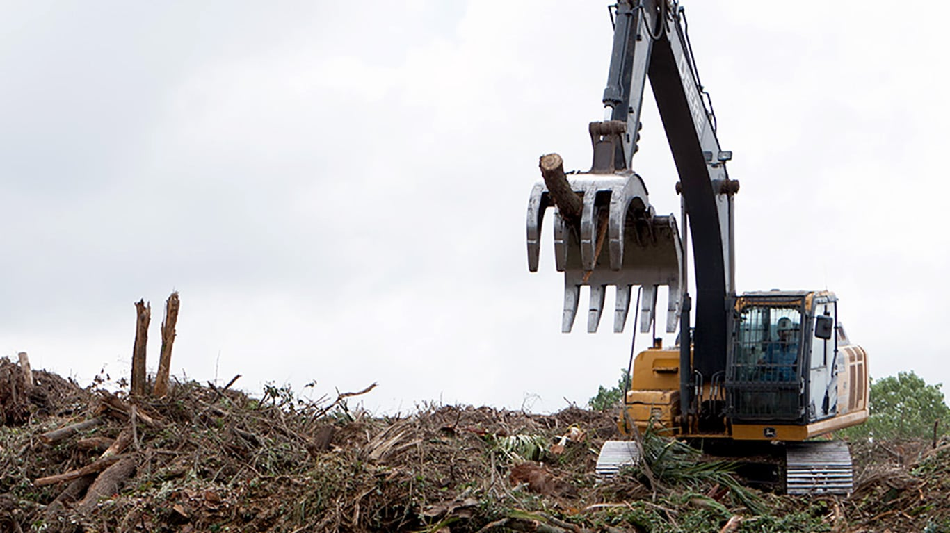 An excavator sorts through a pile of scrap wood