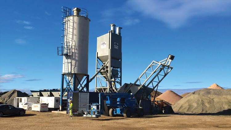 Mixing machine surrounding by piles of materials for cement