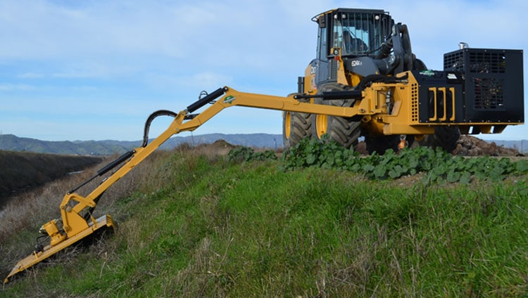 Diamond Mower Attached to a John Deere Wheel Loader on the Side of a Hill