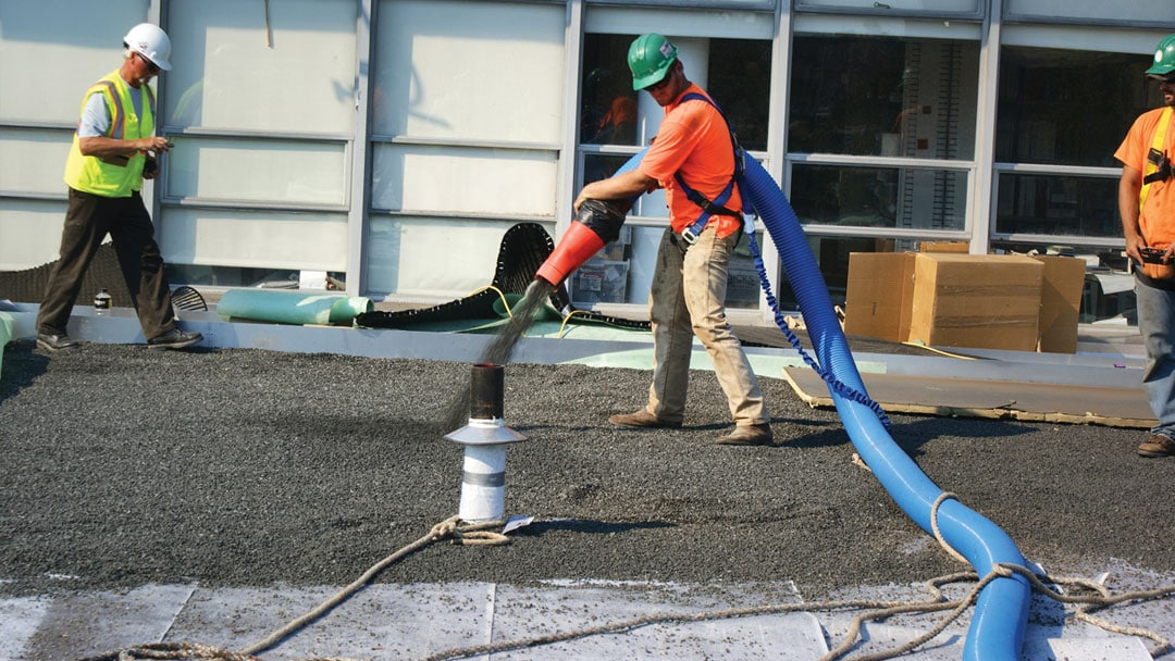 Workers use Express Blower equipment to apply materials to create a green roof.