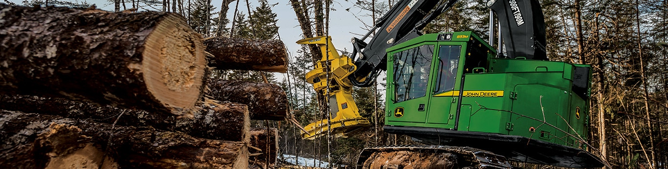 853M Feller Buncher in the woods cutting trees with a FR22B head