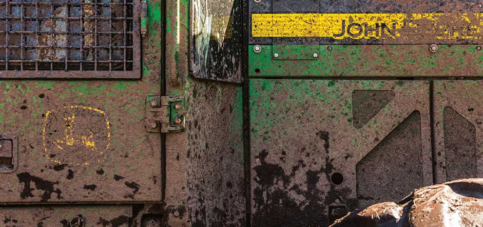 Extreme close up of John Deere forestry machine covered in mud