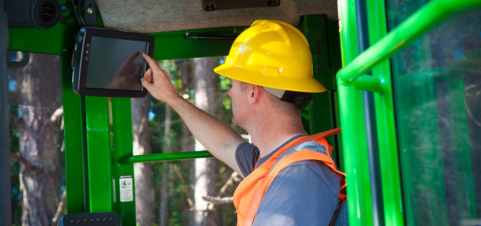 Man using touch screen inside forestry equipment