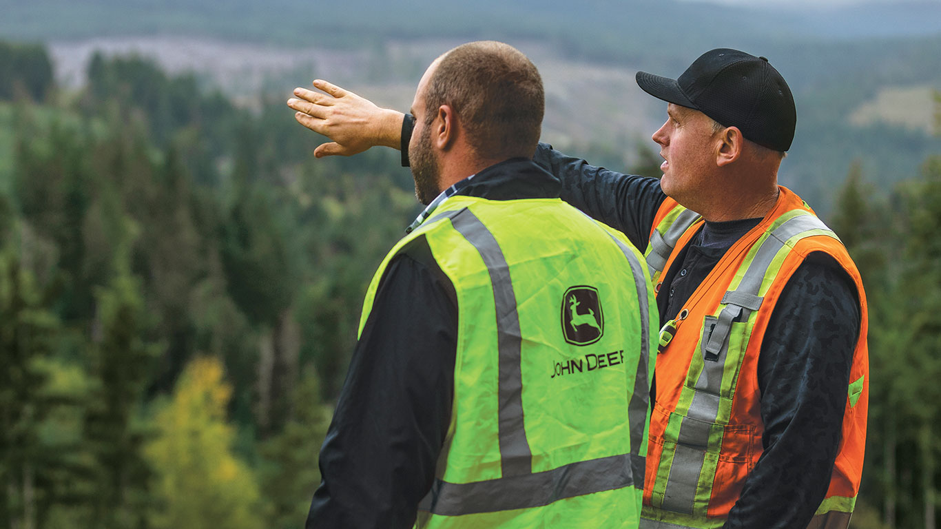 John Deere dealer and customer standing on the side of the mountain looking at the forest below