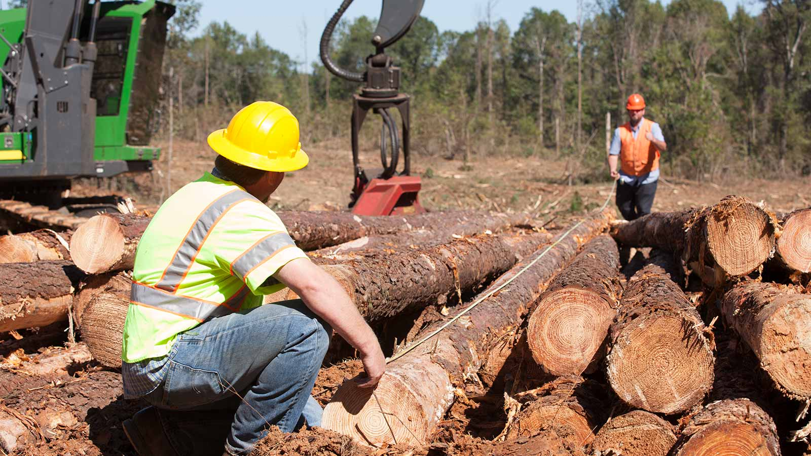 Clark Snipes and Jess Alexander of Oakland Wood Products measuring logs with a John Deere 2154G Swing Machine in the background.