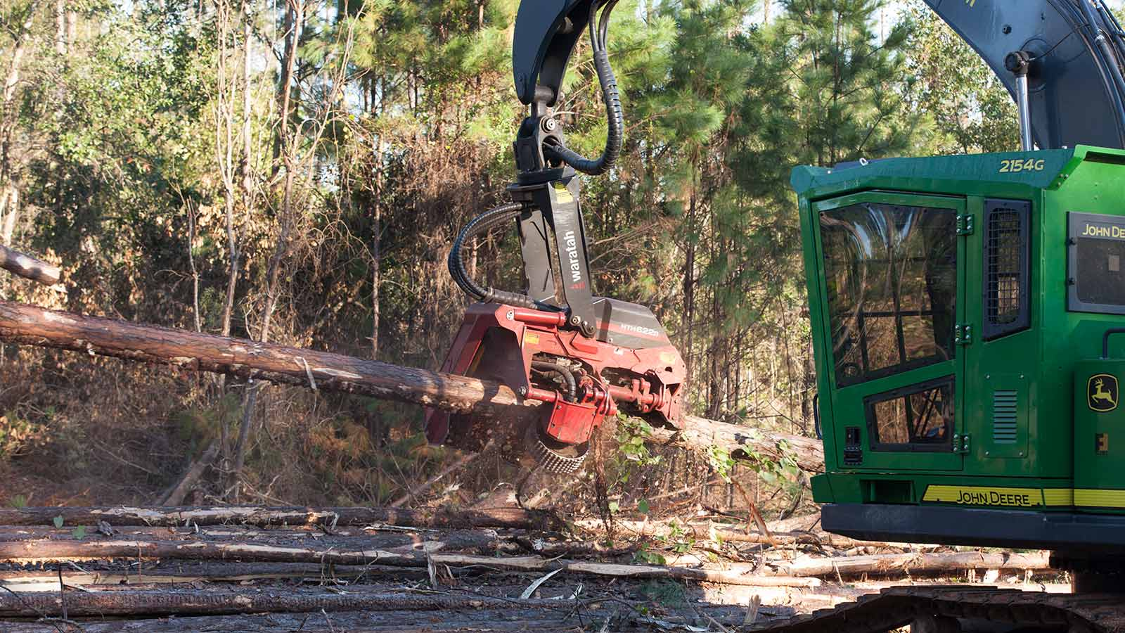 John Deere 2154G Swing Machine equipped with a Waratah HTH622B head cutting limbs from logs.
