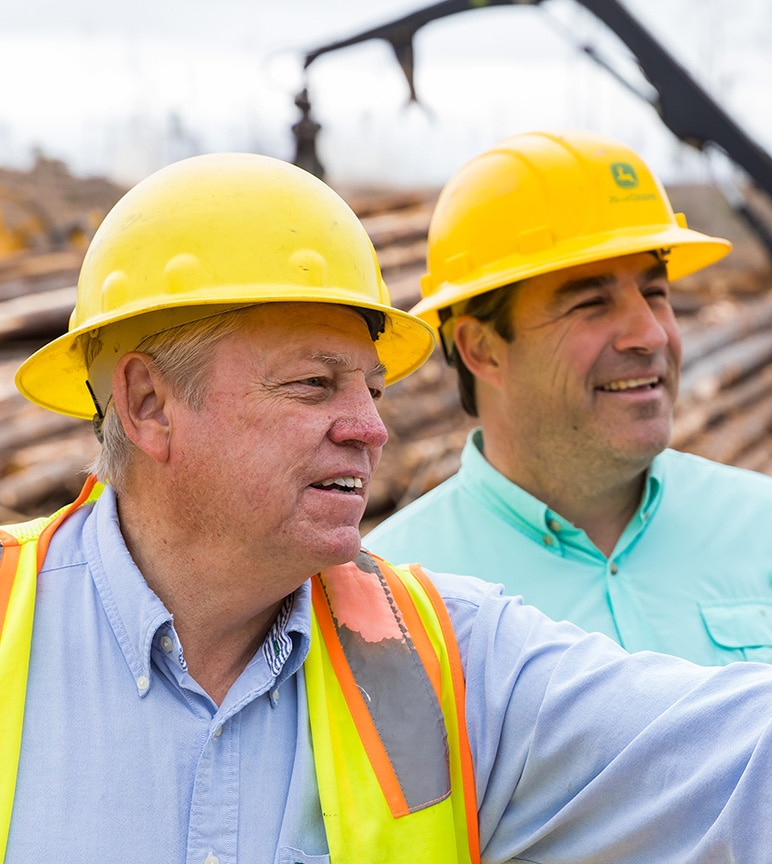 Two men on a logging jobsite smile in front of a log pile