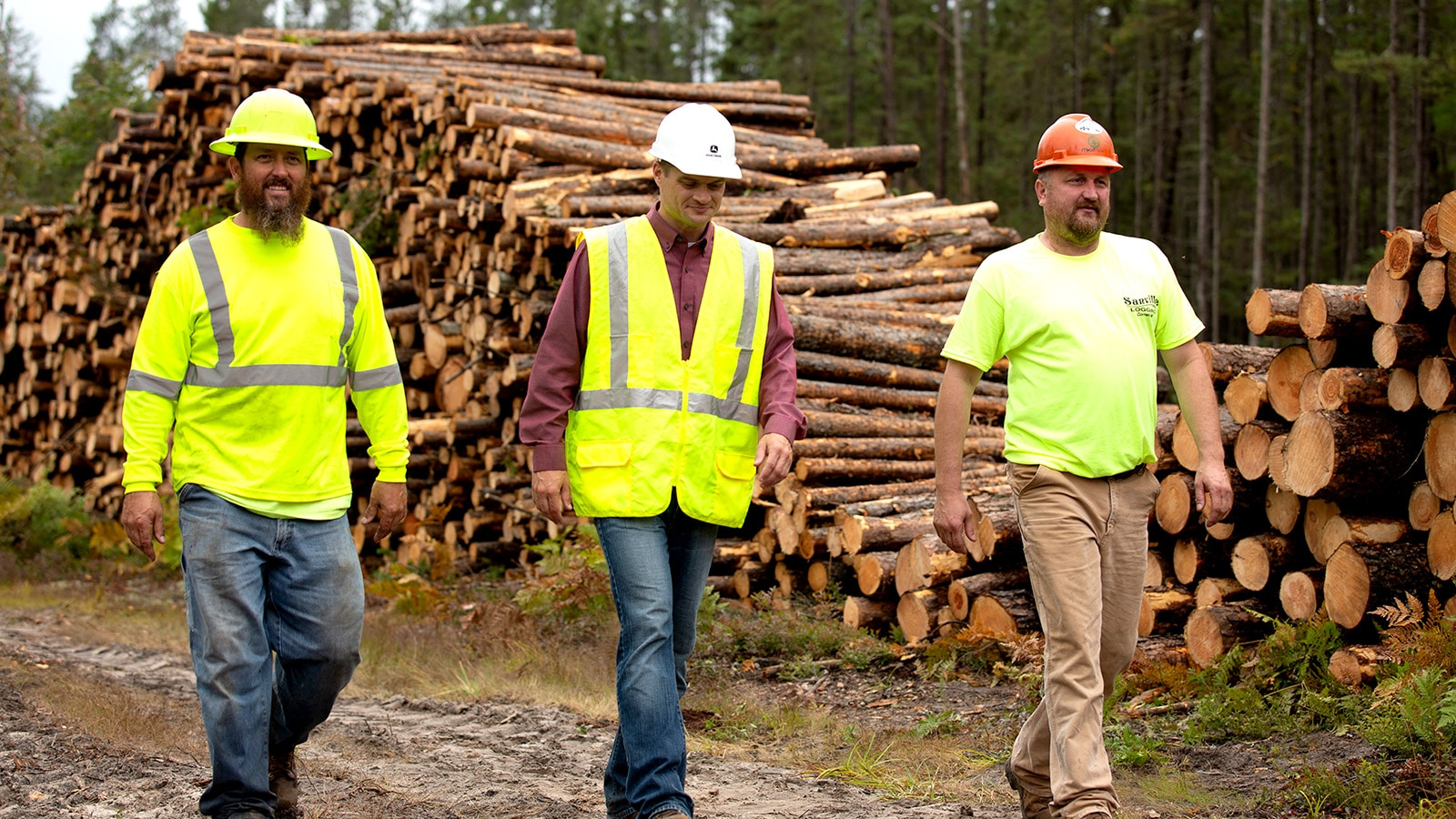 Three men walk in front of a large stack of cut logs.