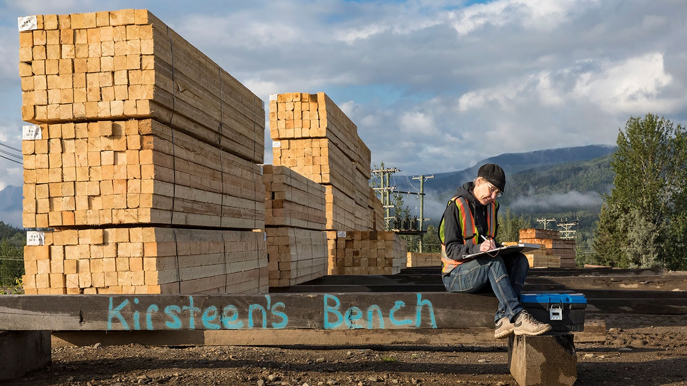 Kirsteen Laing working off a clipboard while sitting on a homemade bench next to stacks of lumber.