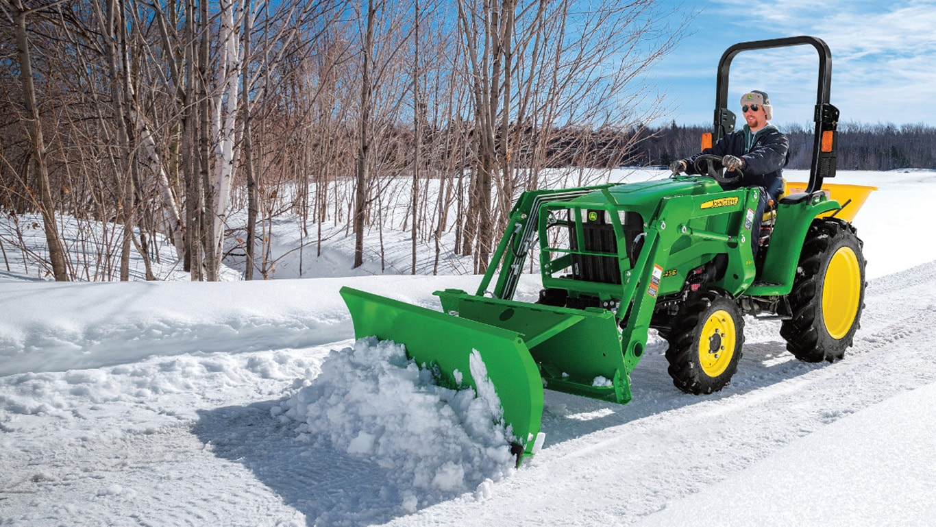 John Deere front end loader with snow blade clears a path