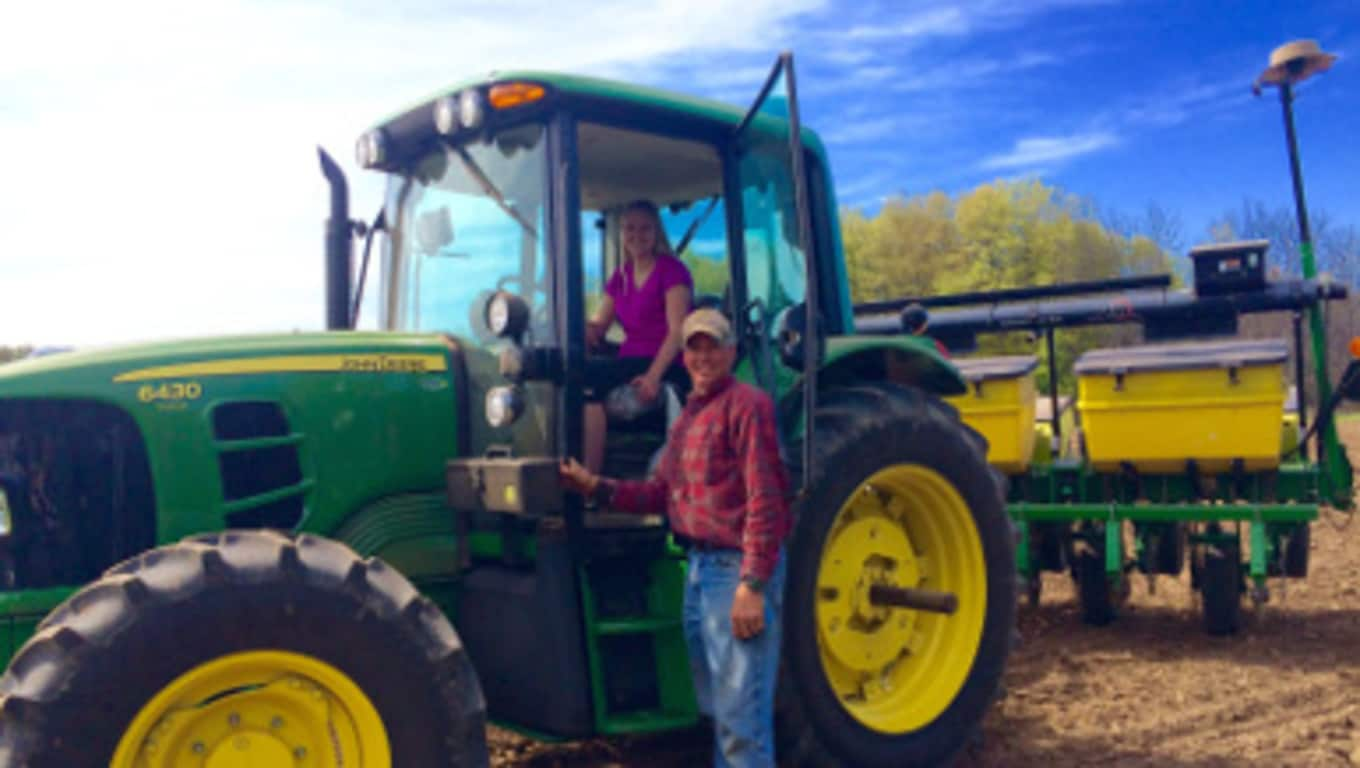 Hanna sits in a John Deere tractor, while her father stands