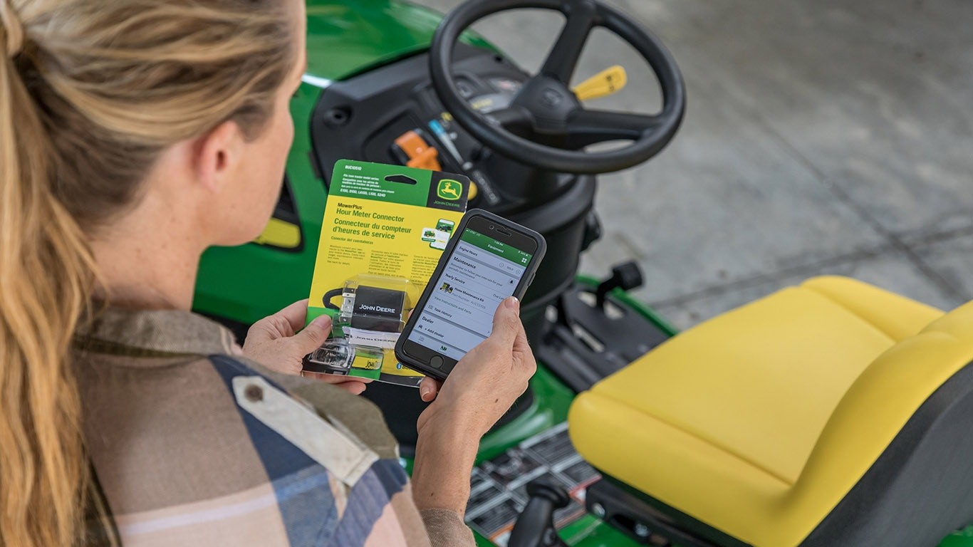 Woman holding a phone with the MowerPlus app open
