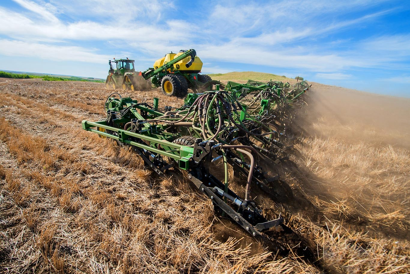 The John Deere 1870 air seeder working in a brown field