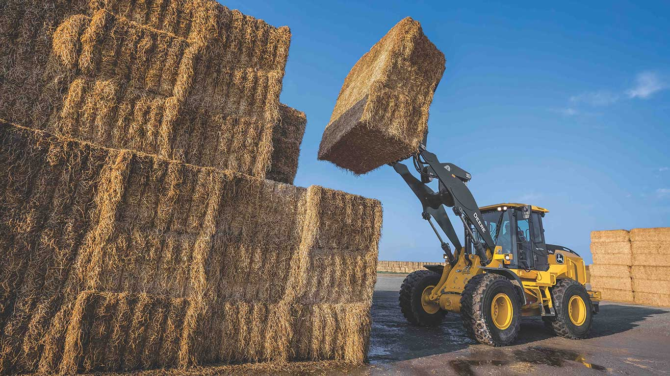 544L long-reach wheel loader on a farm, placing three hay bales on top of a large stack of bales.