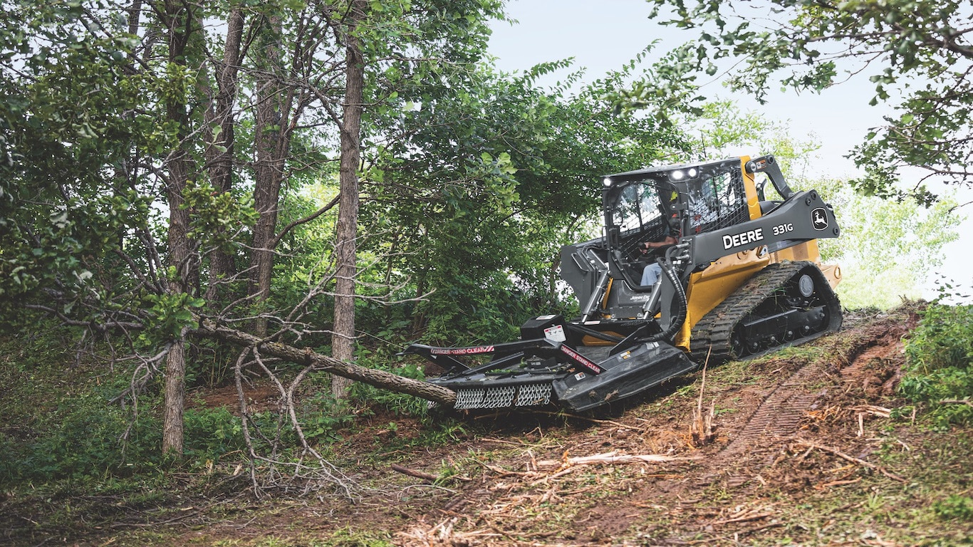 331G with Rotary Cutter attached on a hill cutting down a tree