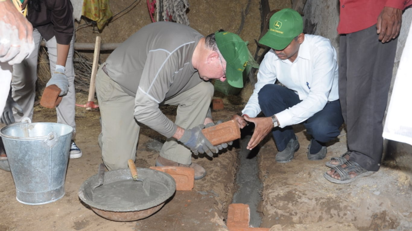 John Deere CEO Sam Allen assists farmers by laying bricks to build a trough in rural India.