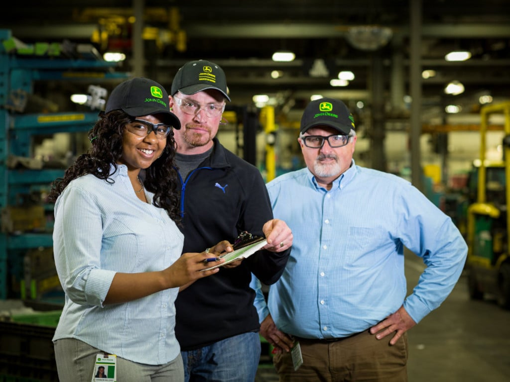 Three John Deere factory employees posing in a factory with safety glasses on