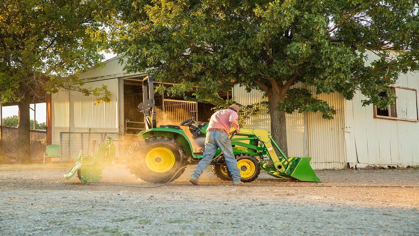 pressure washing tractor in farm yard