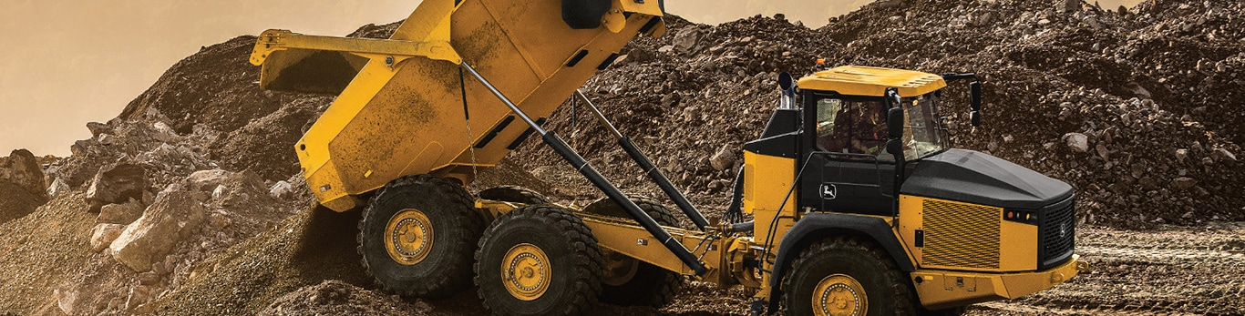 John Deere 460E Dump Truck dumps a load of dirt