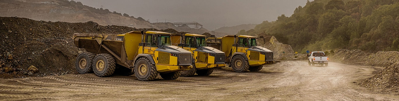 3 articulated dump trucks lined up to receive loads