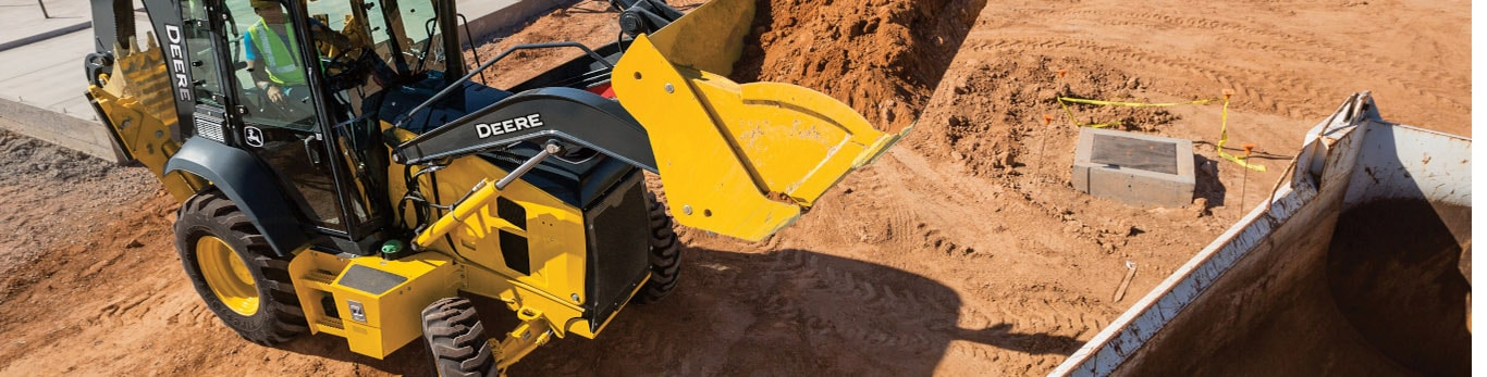 John Deere Backhoe hauling dirt on construction site