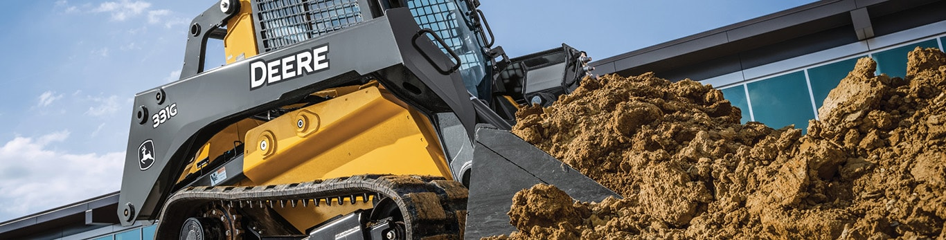 compact track loader moves stone blocks