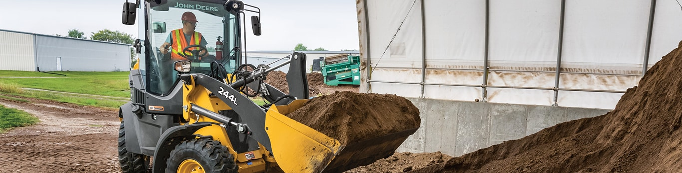 244L compact wheel loader picks up a scoop of dirt from a large pile